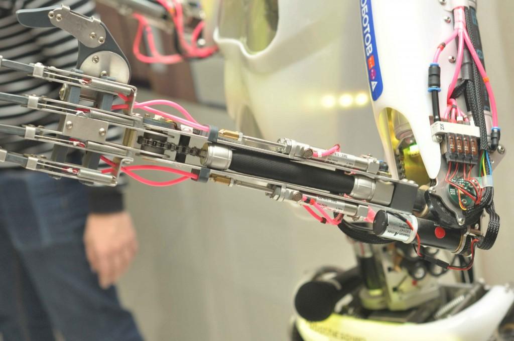 Интересен он и конструктивно. В основе металлический каркас, а приводы - пневматические (!). Пневматика (пневмо приводы и пневмомускулы) позволяет сделать его абсолютно тихим (гудения электросервориводов нет и в помине) и очень естественным в своих движениях. Но есть и обратные стороны таких решений: безумная цена и компрессорная станция, спрятанная в стороне, поскольку в тело робота спрятать такую громоздкую конструкцию некоим образом не возможно.